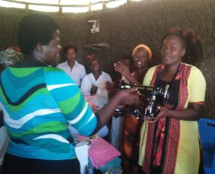COMPE cordinator hands over a sewing machine to the Jaketch ratego group